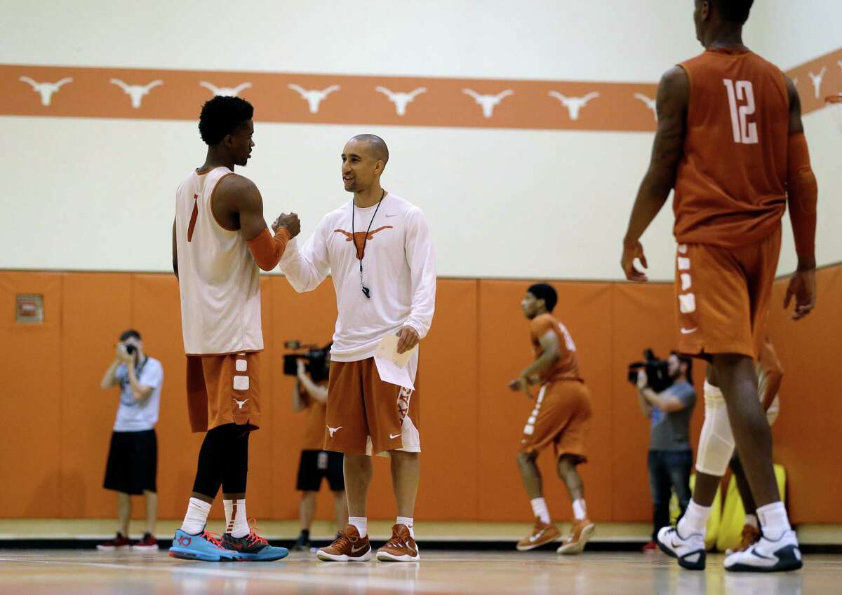 New Texas head basketball coach Shaka Smart, right, talks with guard Isaiah Taylor during practice at the team's facility. Smart is the first African-American men's basketball coach at Texas.