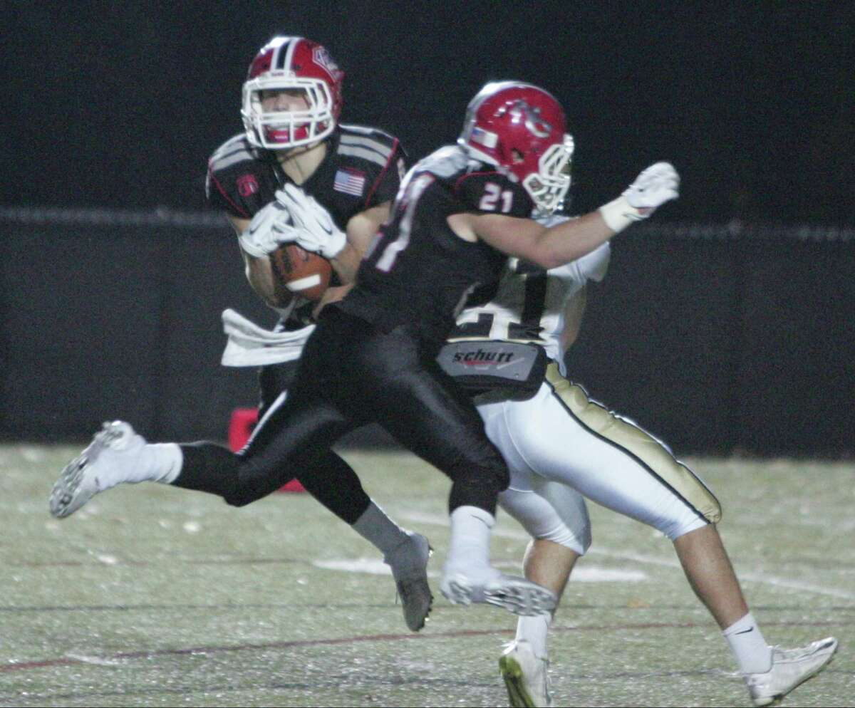 New Canaan's Andrew DeFranco makes an interception with teammate Mike Cognetta on Trumbull's Peter Raverta during a varsity football game in New Canaan Nov. 6, 2015.