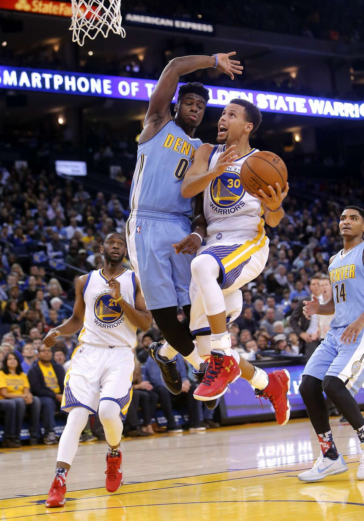 Warriors' Stephen Curry, 30 goes up for a basket in the second quarter as he is guarded by the Nuggets' Emmanual Mudiay, 0 as the Golden Sate Warriors take on the Denver Nuggets at the Oracle Arena in Oakland, Calif. on Fri. November 6, 2015.