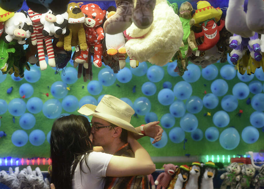 Caitleigh Mann, 17, gives her boyfriend James Bares, 16, a kiss after he wis her a prize at a carnival game at the 46th annual Groves Pecan Festival Friday night in Lion's Park. The event continues through the weekend.  Photo taken Friday, November 6, 2015  Kim Brent/The Enterprise Photo: Kim Brent / Beaumont Enterprise