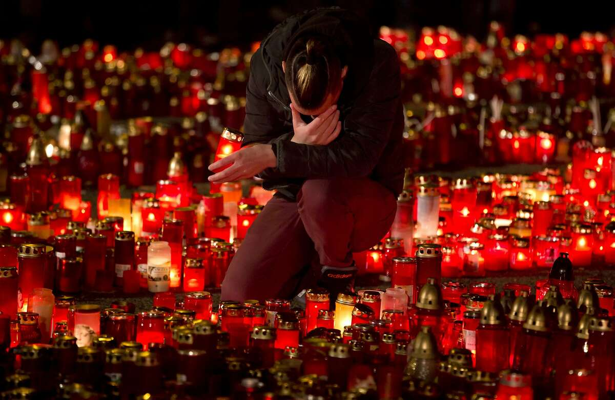 A man touches his forehead holding a candle outside the Colectiv nightclub in Bucharest, Romania, Friday, Nov. 6, 2015, as people mark one week since a deadly fire started during a concert. Romanian prosecutors on Friday questioned an owner of the nightclub where a fire killed 32 people and injured 180.