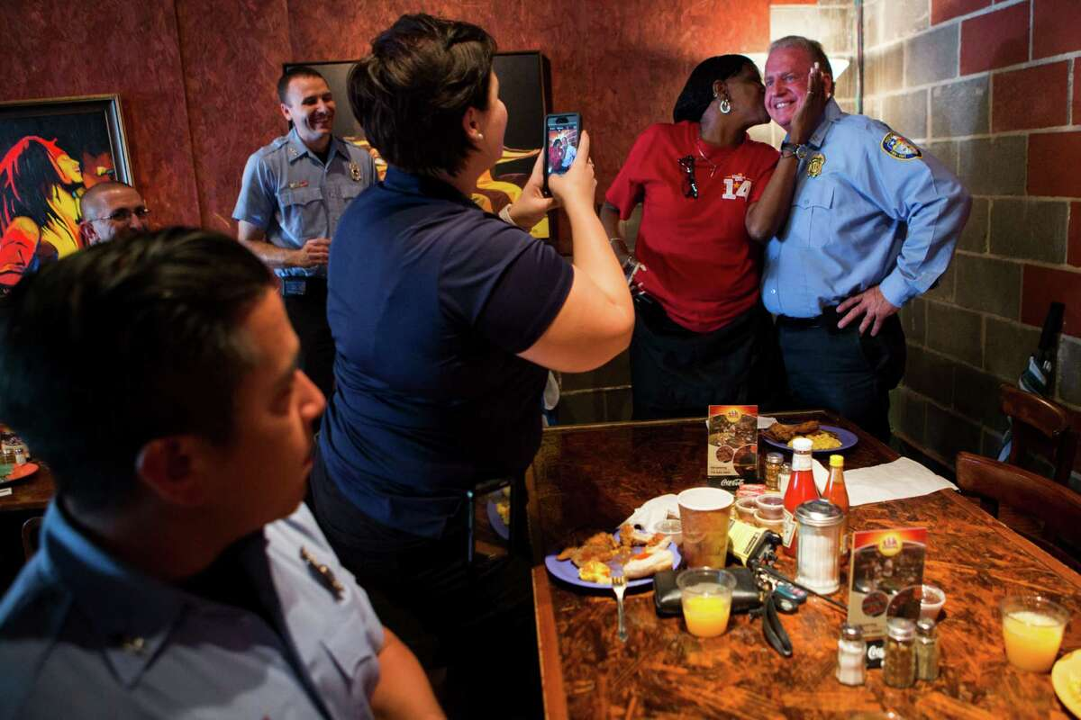 Jacqueline McKnight, 58, kisses Houston Fire Department ems supervisor Nathan Snowden for a photograph during an event at The Breakfast Klub to give McKnight the opportunity to meet and get to know the rescuers that saved her life three years ago. Every time McKnight identifies a HFD member stoping at The Breakfast Klub she thanks them for their service to the community. Friday, Nov. 6, 2015 in Houston.
