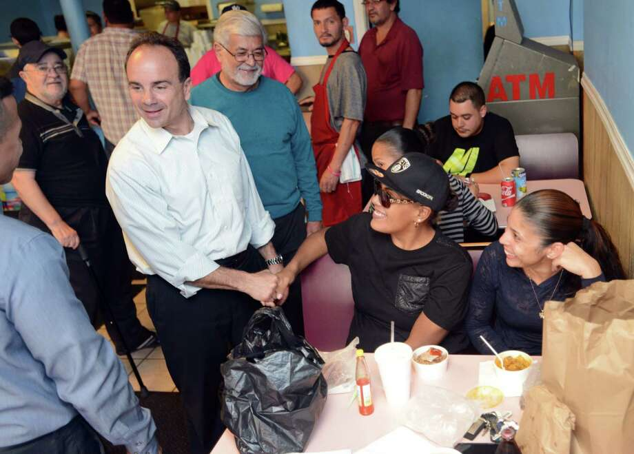 Mayor-elect Joe Ganim shakes hands with Erica Andino as she has lunch with Giselle Abraham, right, Friday, Nov. 6, 2015, at El Coquito on East Main Street in Bridgeport, Conn. Ganim visited local businesses on Friday to thank them for their support. Photo: Autumn Driscoll / Hearst Connecticut Media / Connecticut Post