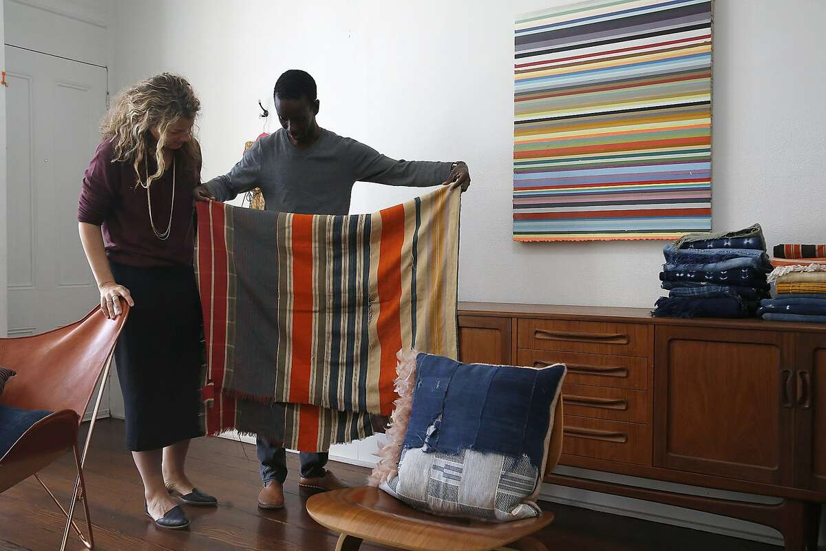 Petel founders Julie Wagne (left) and her husband Ibrahima Wagne (middle) show his great grandmother's blanket at home in San Francisco, Calif., on Friday, November 6, 2015.