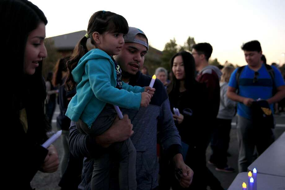 Andy Galaviz holds his daughter Natalie, 3, as she clasps an electric candle during a vigil at UC Merced in Merced, California, on Friday, Nov. 6, 2015. Photo: Connor Radnovich, The Chronicle