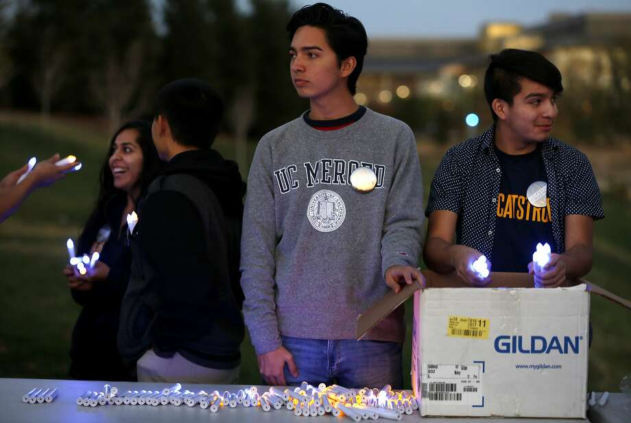 Students Luis Rodriguez (center) and Francisco Ortiz (right) pass out electric candles before a vigil at UC Merced in Merced, California, on Friday, Nov. 6, 2015. Photo: Connor Radnovich, The Chronicle