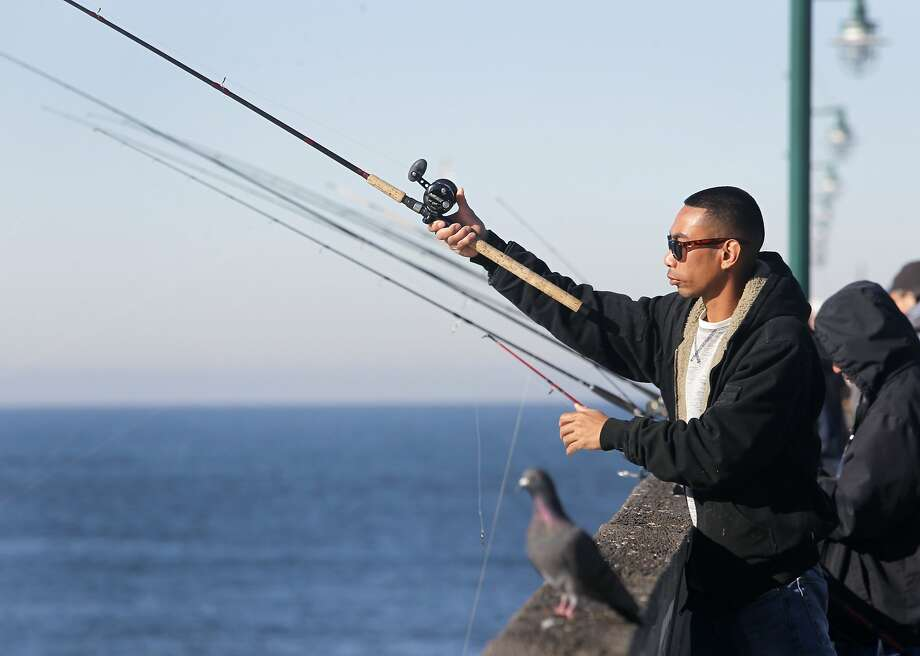 Weslie Mata casts a fishing line off the municipal pier in Pacifica, Calif. on Saturday, Nov. 7, 2015. Mata was hoping to catch Dungeness crab but had to settle on fishing for surf perch or striped bass instead. A ban on recreational crabbing has been ordered by the state Fish and Game Commission because of potential domoic acid toxicity. Photo: Paul Chinn, The Chronicle