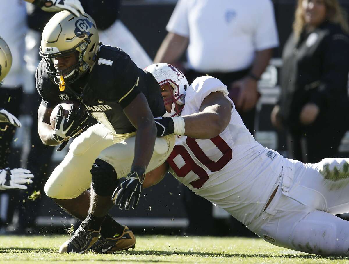 Colorado running back Patrick Carr, left, is pulled down for a loss of yardage by Stanford defensive end Solomon Thomas in the second half of an NCAA football game Saturday, Nov. 7, 2015, in Boulder, Colo. Stanford won 42-10. (AP Photo/David Zalubowski)
