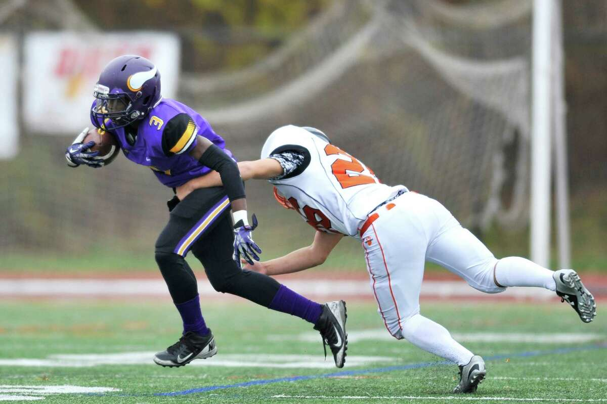 Westhill's Jeremy Young fights off a tackle during a Saturday afternoon game against Ridgefield at Westhill High School on Nov. 7, 2015.