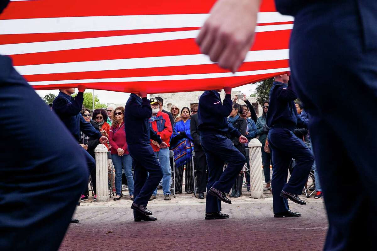Crowds watch as airmen march with the American Flag during the U.S. Military Veterans Parade Saturday, Nov. 7, 2015 in front of the Alamo. The Veterans Day parade is known as the biggest in Texas as veterans, active-duty members and their families and friends participate in the parade parade since Veterans Day 2000.
