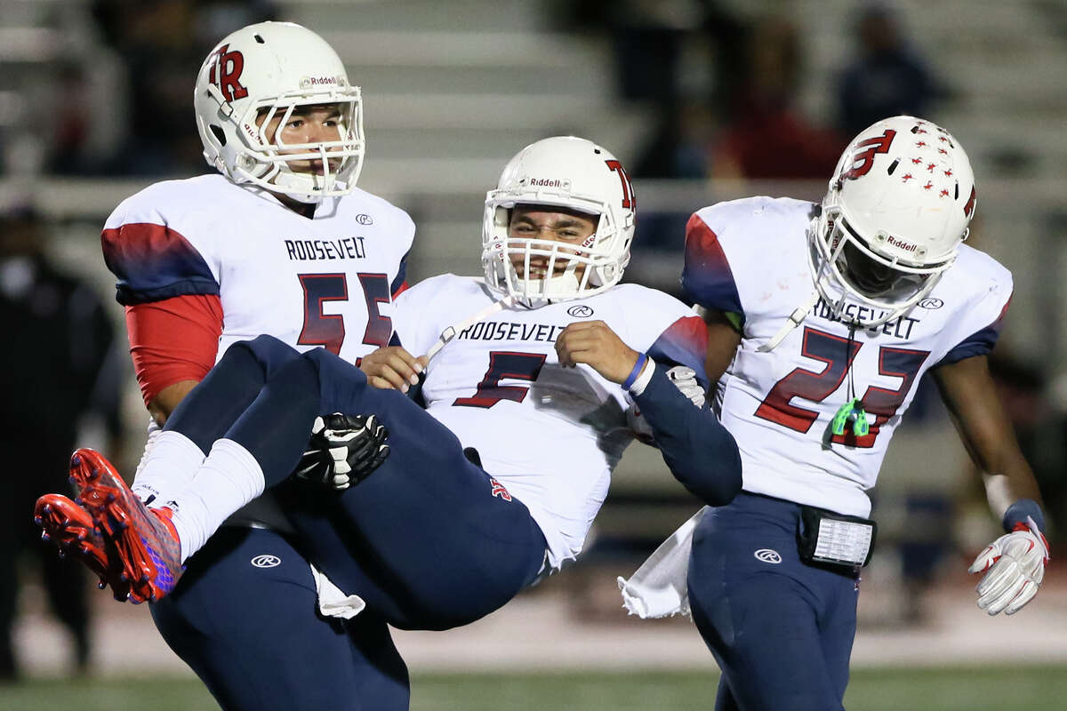 Roosevelt's Manuel Hernandez (left) carries Bryson Carroll off the field accompanied by Joshua Morgan during the second half of their District 26-6A game with Churchill at Comalander Stadium on Oct. 24, 2015. Churchill beat Roosevelt 37-14.
