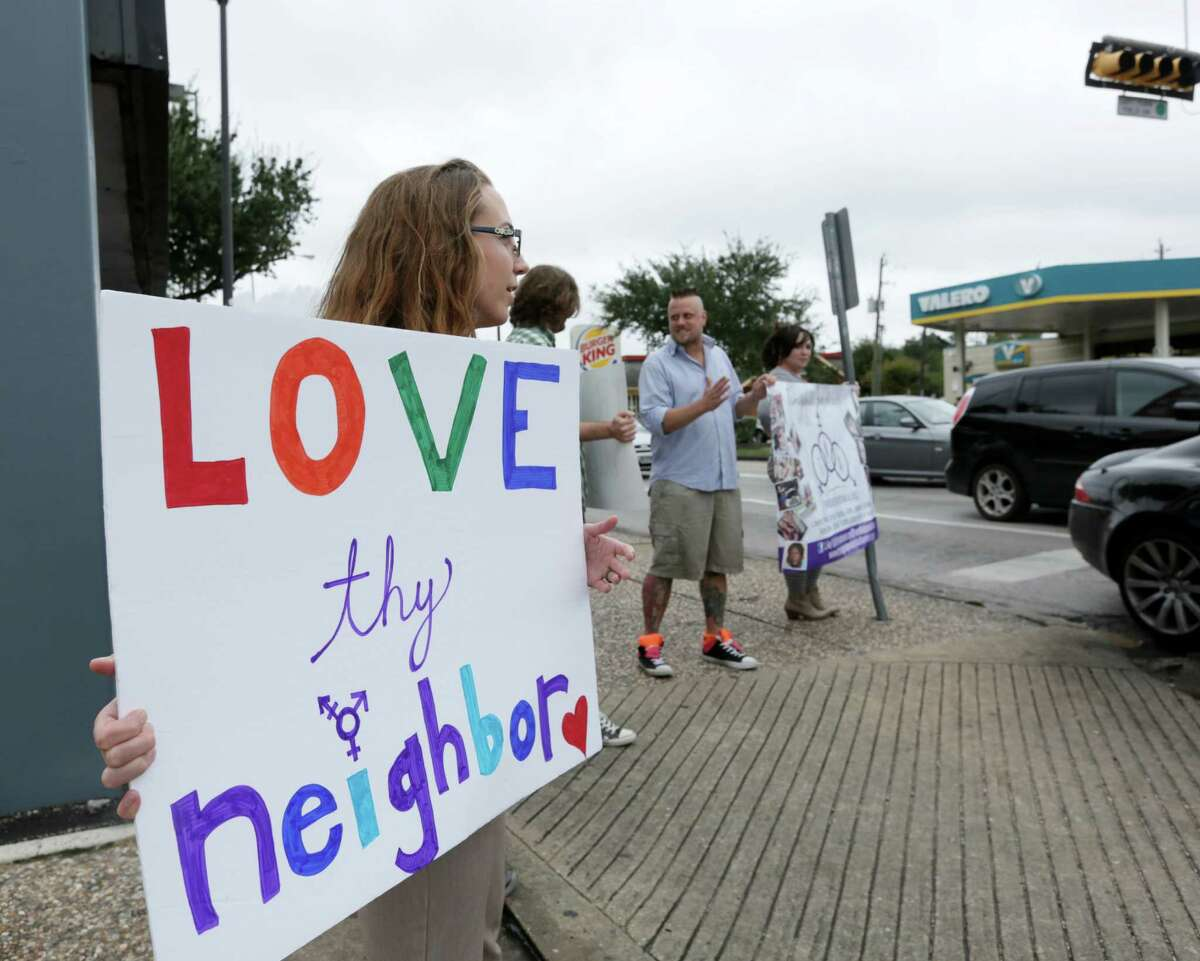 Heather Ringo, left, holds a sign at a rally for awareness of the transgender community, at the corner of Montrose Boulevard and Westheimer Road, Saturday, Nov. 7, 2015, in Houston.