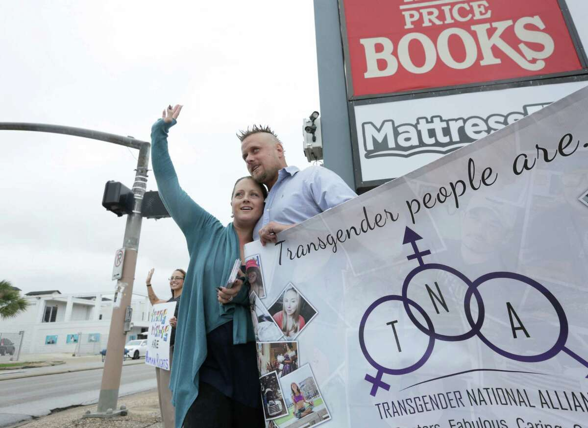 Nikki Araguz Loyd waves to traffic with her husband William Loyd at a rally for awareness of the transgender community, at the corner of Montrose Boulevard and Westheimer Road, Saturday, Nov. 7, 2015, in Houston.