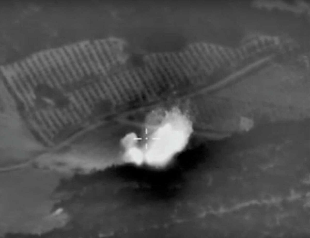 This photo made from the footage taken from Russian Defense Ministry official web site on Monday, Oct. 5, 2015 shows an attack made from a fighter jet in Syria. Russian Defense Ministry describes the incident as an airstrike against an ISIS ammunition depot near Talbiseh settlement (Homs). The object is completely destroyed. (Russian Defense Ministry Press Service via AP)