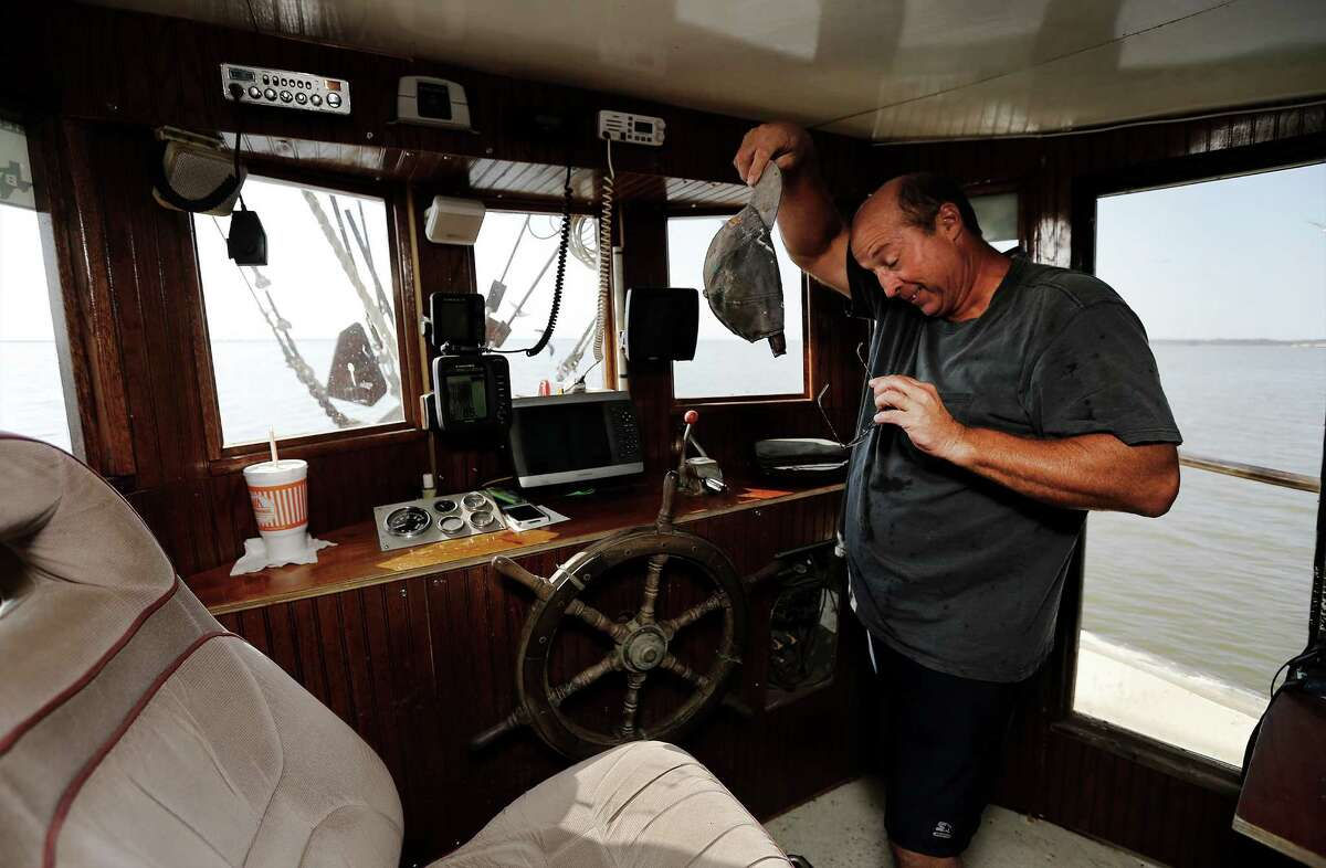 Shrimper Dwayne Harrison wipes away sweat from he forehead as he sets out for the Houston Ship Channel near Baytown, Texas late in the afternoon in search of shrimp on Thursday, Oct. 29, 2015. Harrison's family has been in the seafood business for two generations. He bought his own boat after getting out of the petro-chemical business in the 90's and has been scratching to make a living ever since in shrimping. (Kin Man Hui/San Antonio Express-News)