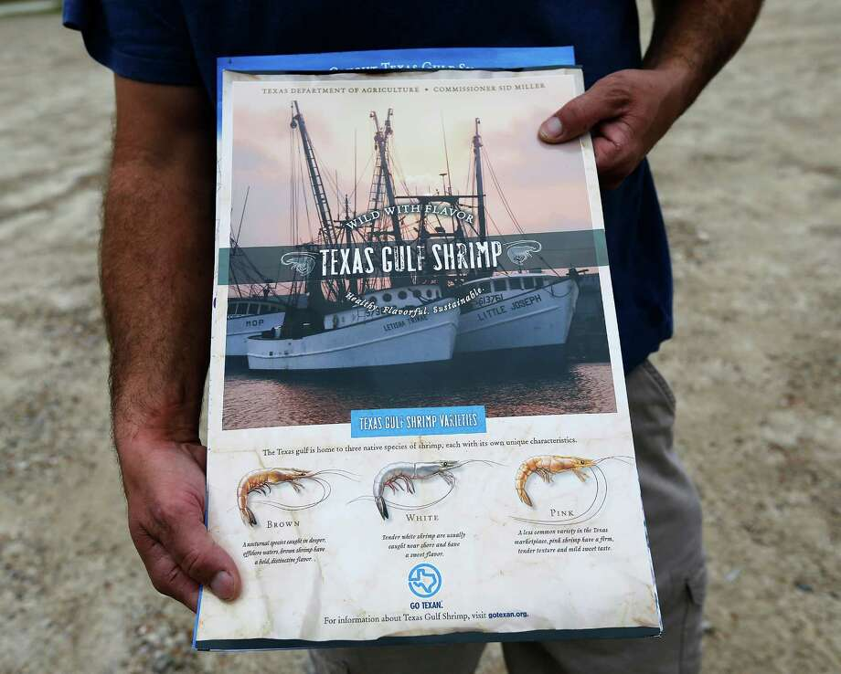Jack Blume of JB's Seafood in Crystal Beach, Texas holds signage created by the Texas Department of Agriculture to promote Texas Gulf shrimping on Friday, Oct. 30, 2015. Blume is a fourth-generation shrimper whose family has lived on the Bolivar Peninsula as one of the first family of settlers in the area. Blume said his business is struggling against competition and rigid rules and worries that he may be the last generation of his family to stay in the business.  (Kin Man Hui/San Antonio Express-News) Photo: Kin Man Hui, Staff / San Antonio Express-News / ©2015 San Antonio Express-News