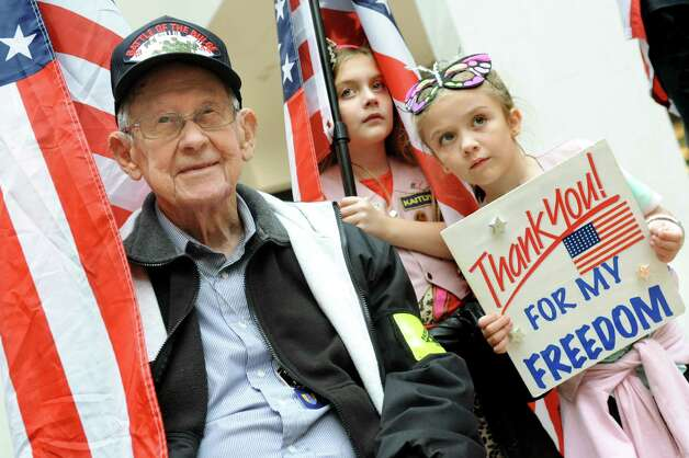 WWII veteran Kenneth Bailey, 93, of Voorheesville, left, joins sisters Kaitlyn Farron, 8, center, and Sydney Farron, 6, of Wynantskill during an event to honor veterans and build support for the Holiday Military Support Drive on Saturday, Nov. 7, 2015, at Colonie Center in Colonie, N.Y. Bailey, who still rides his motorcycle, is a member of the Patriot Guard Riders and the girls are Pink Patriots. (Cindy Schultz / Times Union) Photo: Cindy Schultz