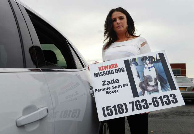 Rose VanAlstyne stands next to her car as she holds a poster for her missing dog, Zada, who has been absent for three weeks, Friday, Nov. 6, 2015, in Albany, N.Y. Zada jumped from the open rear window of her car. Rose has put up hundreds of signs, hired dog trackers, talked to an animal psychic, and placed trail cameras at selected locations. VanAlstyne has spent thousands trying to find the dog, a Boxer who was lost in Menands. (Will Waldron/Times Union) Photo: Will Waldron / 00034123A
