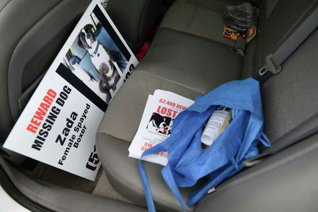 Poster, fliers and a bag of dog food sit in the back seat of Rose VanAlstyne's car where her dog, Zada, escaped from three weeks ago Friday, Nov. 6, 2015, in Albany, N.Y. Rose has put up hundreds of signs, hired dog trackers, talked to an animal psychic, and placed trail cameras at selected locations. VanAlstyne has spent thousands trying to find the dog, a Boxer who was lost in Menands. (Will Waldron/Times Union) Photo: Will Waldron / 00034123A