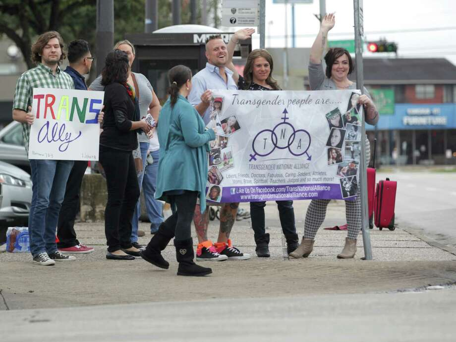 People wave to traffic at a rally Saturday for awareness of the transgender community at the corner of Montrose Boulevard and Westheimer Road. Photo: Jon Shapley, Staff / © 2015  Houston Chronicle