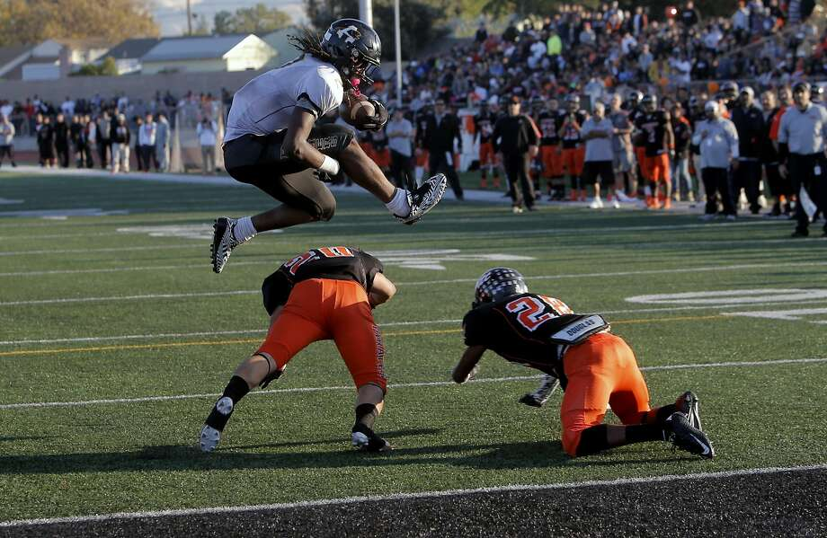 Antioch's Najee Harris goes up and over Pittsburg's Jose Vasquez (left) and Michael Nelson for a fourth-quarter touchdown. Photo: Michael Macor, The Chronicle