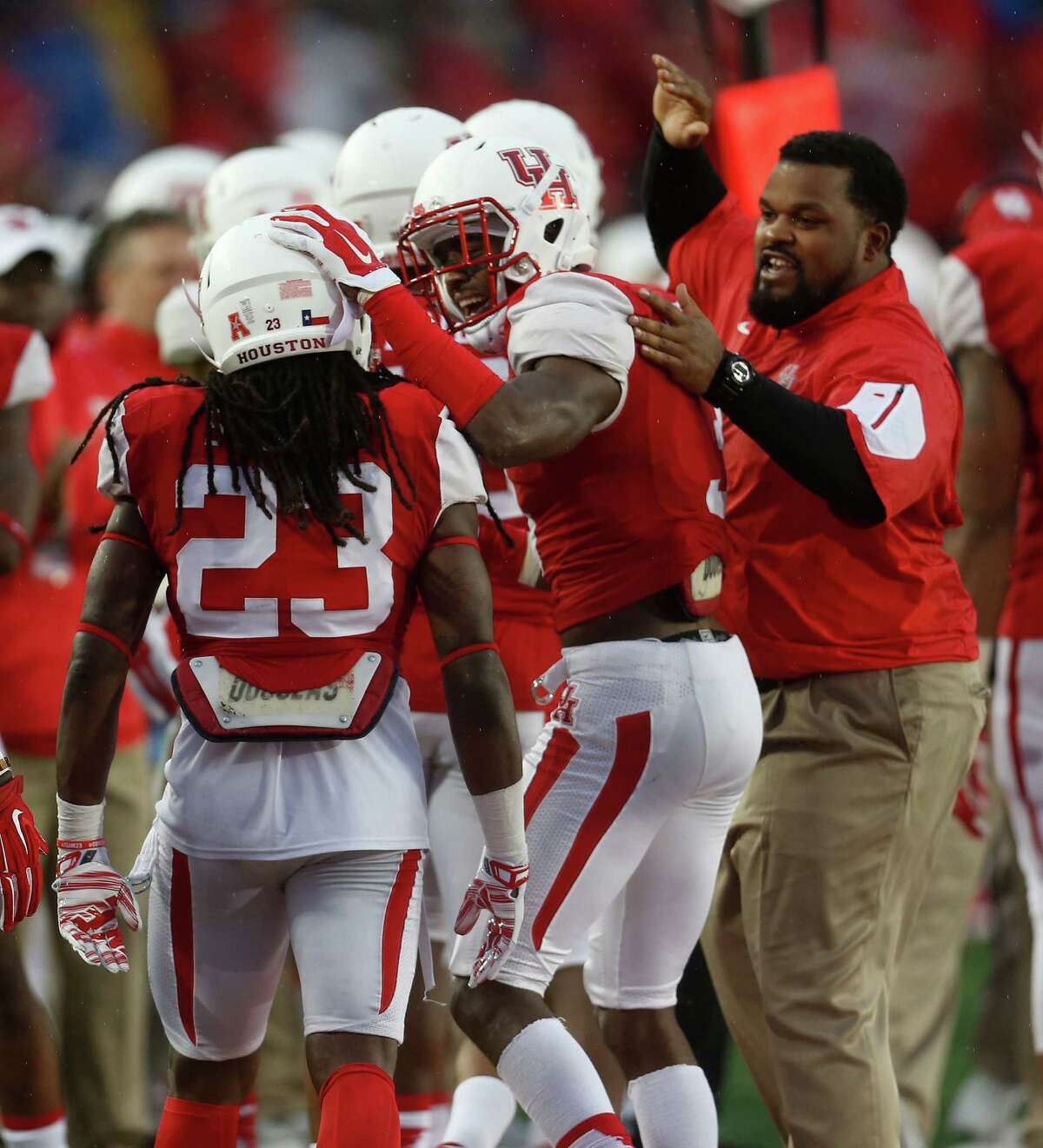 Houston Cougars safety Trevon Stewart (23) celebrates his sack and safety on Cincinnati Bearcats quarterback Gunner Kiel (11) with William Jackson III (3) during the second half of a college football game at TDECU Stadium on Saturday, Nov. 7, 2015.