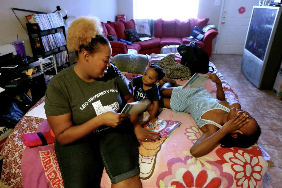 Jessica Vaughn, with nephew Reidyn Hall, 9 months, and daughter Chrysta Jenkins, 8, slept on an air mattress in her mother's home as she searched for a new apartment.