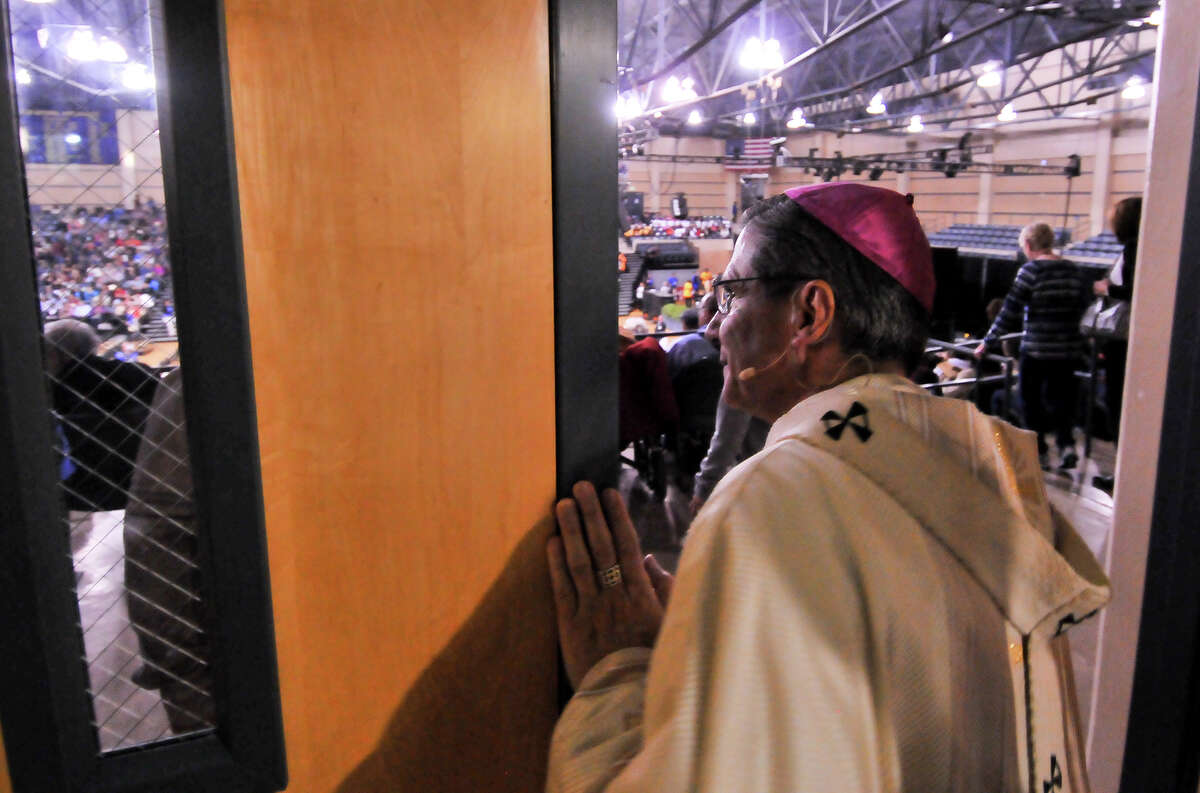 San Antonio Archbishop Gustavo Garcia-Siller peaks into Greehey Arena prior to a mass to celebrate the Archdiocese's Assembly 2015. Over 5000 people attended.