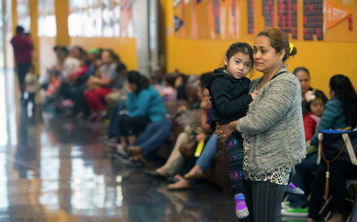 Wimell Rivera holds her daughter, Erika Rivera, 4, as they wait Monday to sign up for the KIPP lottery.