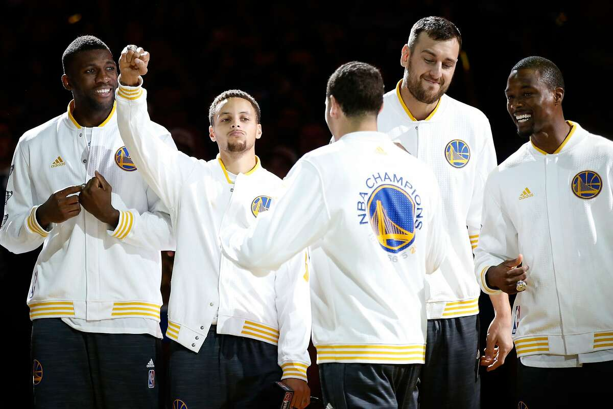 OAKLAND, CA - OCTOBER 27: Festus Ezeli #31, Stephen Curry #30, Klay Thompson #11, Andrew Bogut #12 and Harrison Barnes #40 of the Golden State Warriors celebrate after receiving their championship rings prior to their game against the New Orleans Pelicans in the NBA season opener at ORACLE Arena on October 27, 2015 in Oakland, California. NOTE TO USER: User expressly acknowledges and agrees that, by downloading and or using this photograph, User is consenting to the terms and conditions of the Getty Images License Agreement. (Photo by Ezra Shaw/Getty Images)