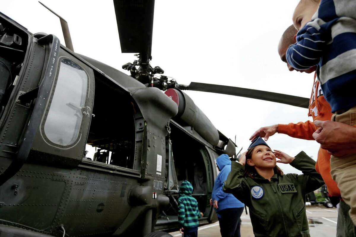 Catalina Montalvo, six, of Austin, shown with father Major David Montalvo, Texas Air National Guard, and brother Michael, 24-months, next to a UH-60 Black Hawk helicopter at the sixth annual Salute to Military Service event to honor and celebrate the armed forces at the Kemah Boardwalk Saturday, Nov. 7, 2015, in Kemah, Texas.