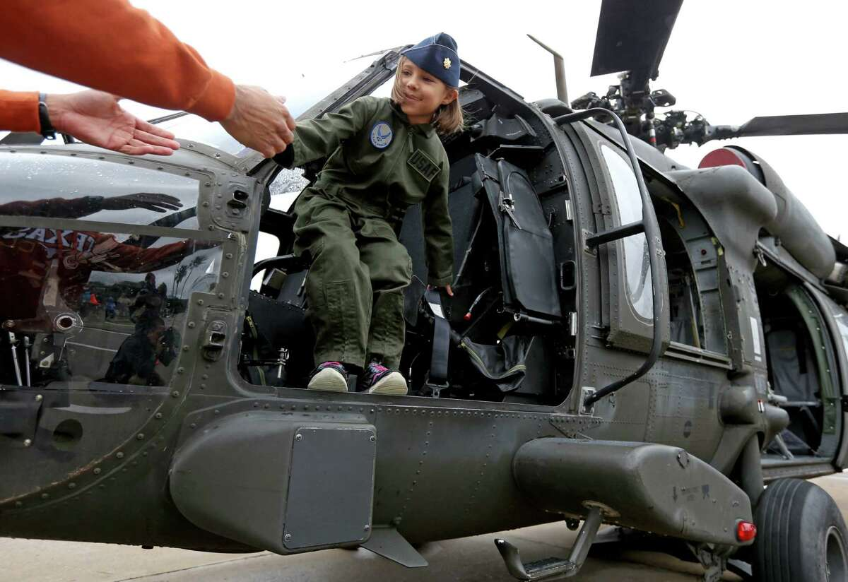 Catalina Montalvo, six, of Austin, gets help from her father Major David Montalvo, Texas Air National Guard, exiting a UH-60 Black Hawk helicopter at the sixth annual Salute to Military Service event to honor and celebrate the armed forces at the Kemah Boardwalk Saturday, Nov. 7, 2015, in Kemah, Texas.