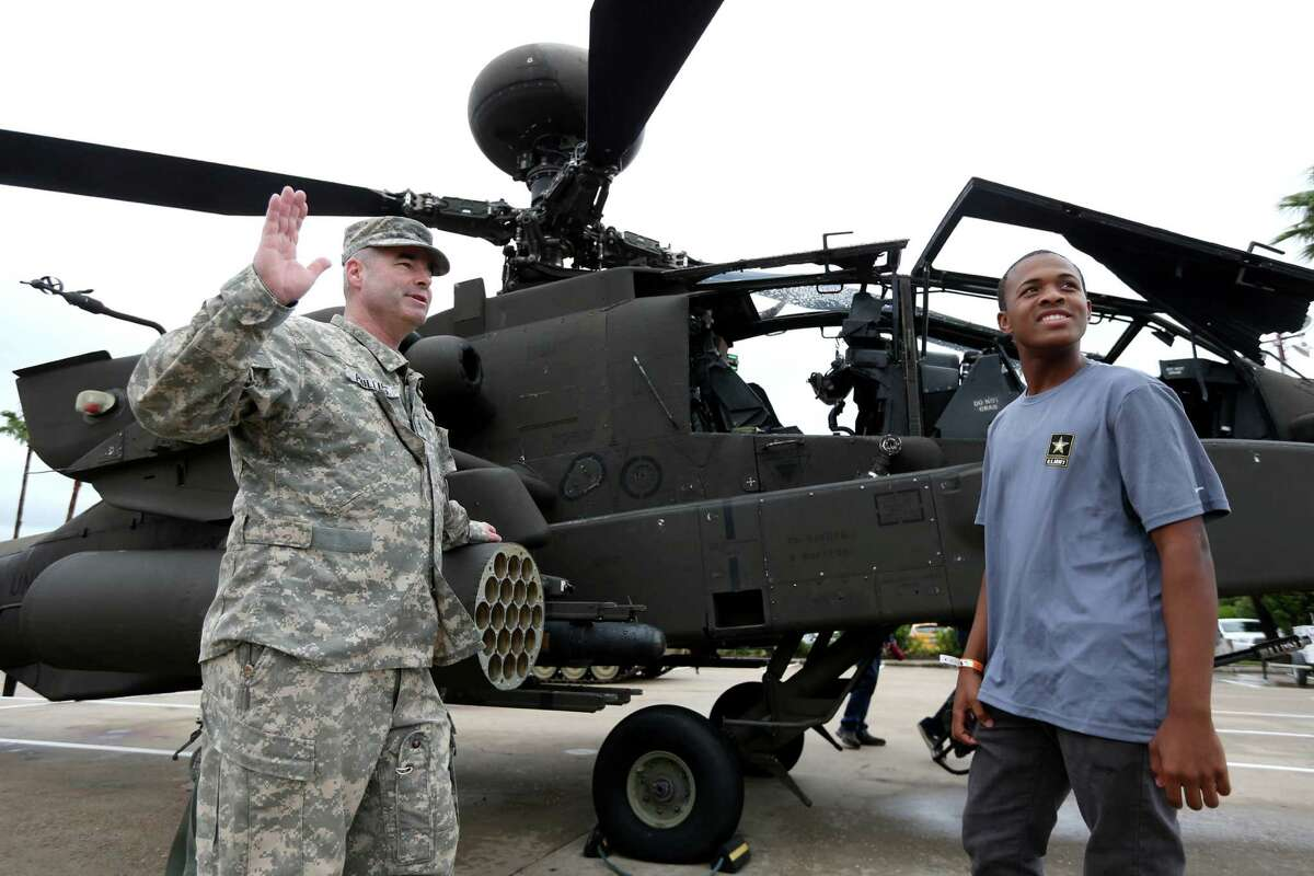Chief Warrant Officer 2 Craig Phillips, U.S. Army reservist, with Davarius Byrd, 18, of Houston, recently enlisted in the U.S. Army, in front of an AH-64 Apache helicopter at the sixth annual Salute to Military Service event to honor and celebrate the armed forces at the Kemah Boardwalk Saturday, Nov. 7, 2015, in Kemah, Texas.