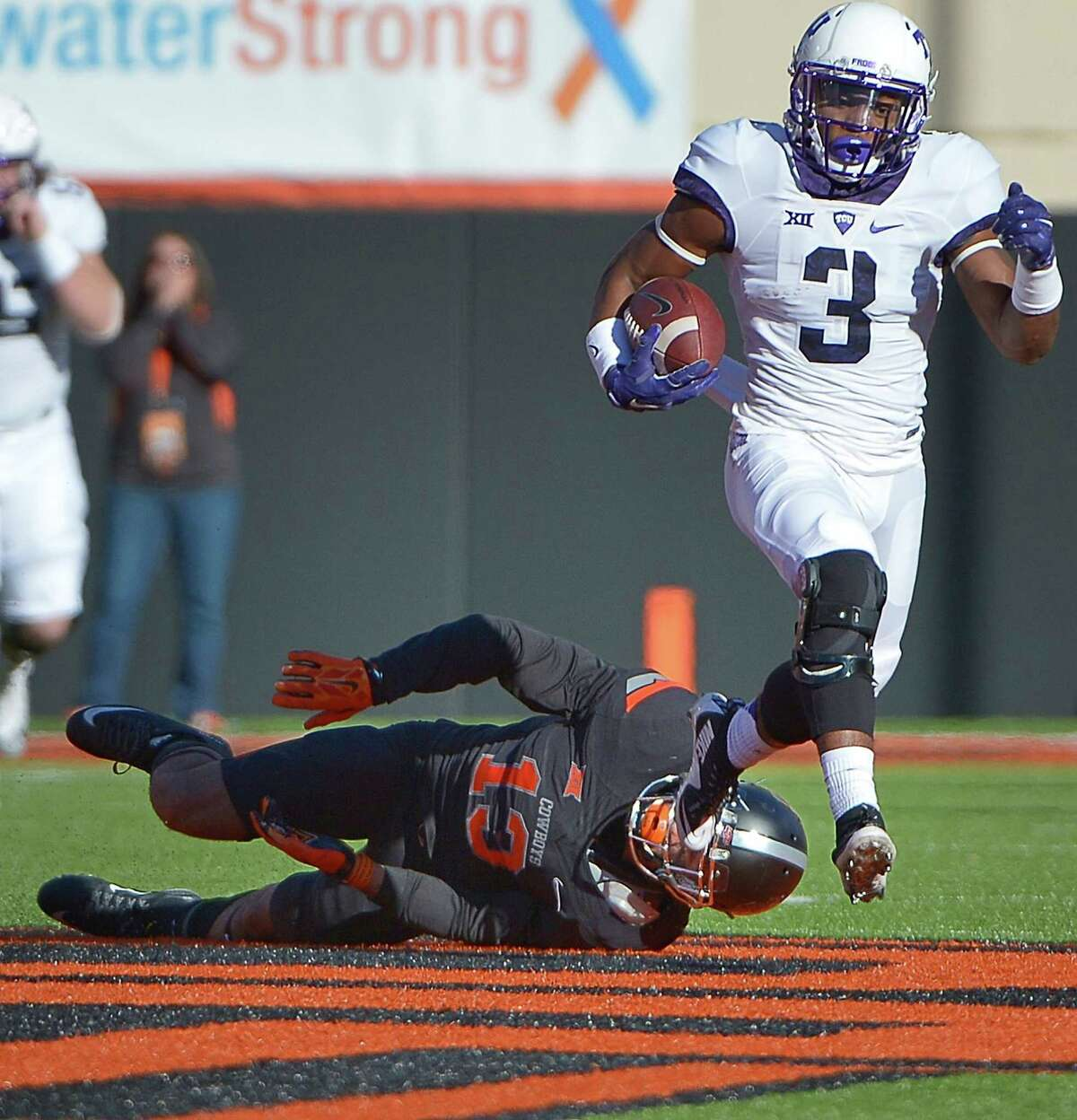 TCU running back Shaun Nixon (3) takes the ball for 70 yards on a pass play, evading Oklahoma State safety Jordan Sterns (13) during the first quarter at Boone Pickens Stadium in Stillwater, Okla., on Saturday, Nov. 7, 2015. The host Cowboys won, 49-29. (Max Faulkner/Fort Worth Star-Telegram/TNS)