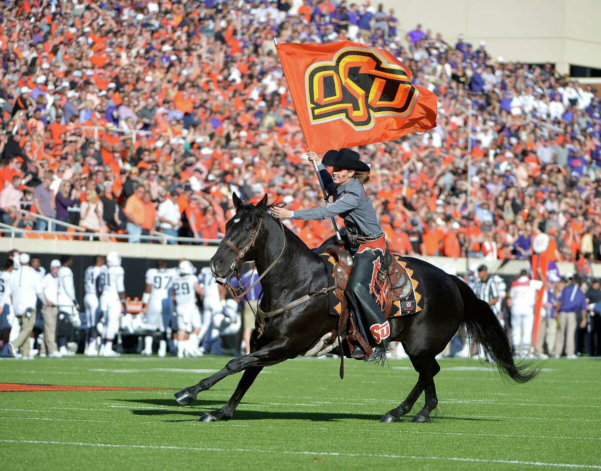 Oklahoma State's Bullet and the Spirit Rider run on to the field after a OSU first-half touchdown against TCU at Boone Pickens Stadium in Stillwater, Okla., on Saturday, Nov. 7, 2015. The host Cowboys won, 49-29. (Max Faulkner/Fort Worth Star-Telegram/TNS)
