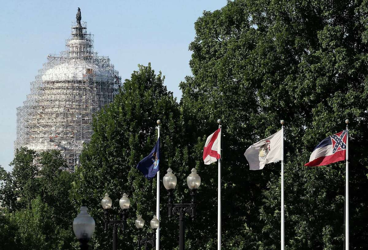 WASHINGTON, DC - JUNE 24: The state flag of Mississippi, which incorporates the flag of the Confederate States of America in the top left corner, is displayed with the flags of the other 49 states and territories in front of Union Station near the US Capitol June 24, 2015 in Washington, DC. In the wake of an apparently racist shooting that left nine African Americans dead in Charleston, South Carolina, Gov. Nikki Haley has asked that the confederate flag, also known as the 'Stars and Bars,' be taken down from in front of the state capitol building, adding political pressure to Mississippi to remove the charged symbol from its flag..(Photo by Mark Wilson/Getty Images)