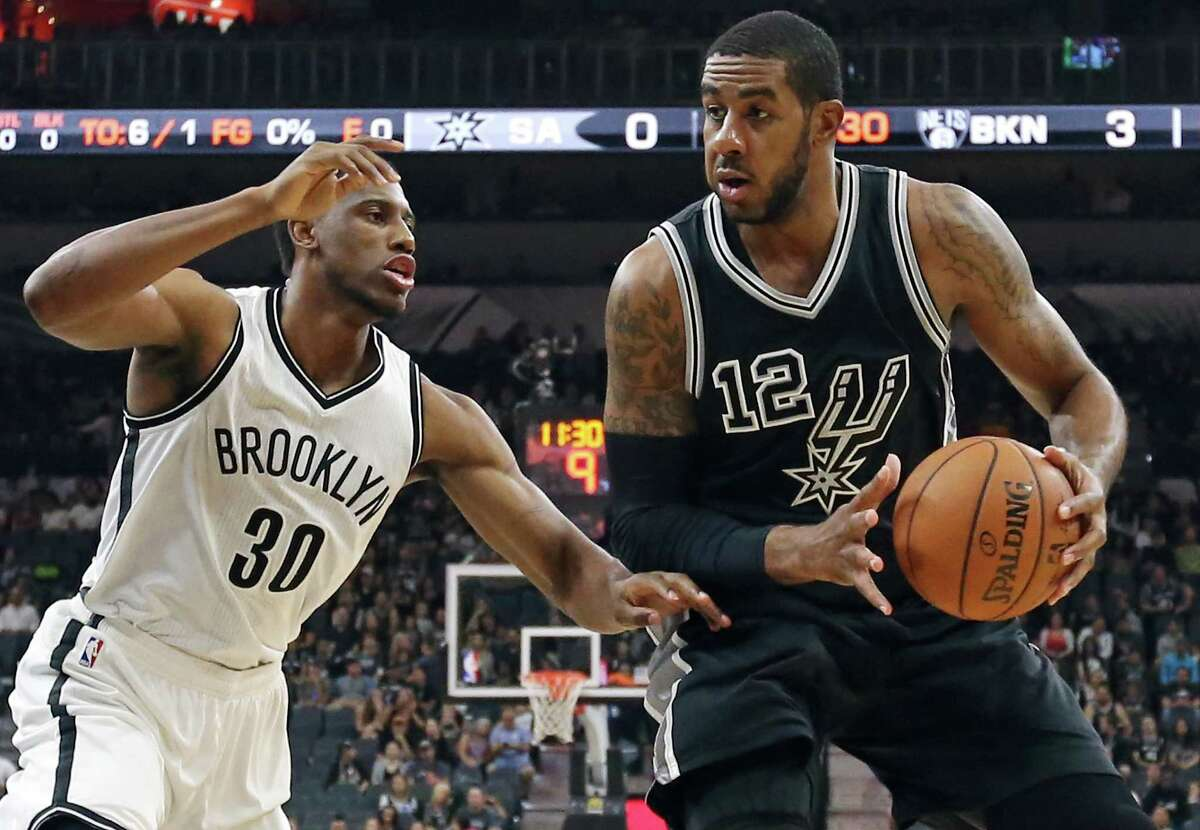 Spurs' LaMarcus Aldridge looks for room around Brooklyn Nets' Thaddeus Young during first half action on Oct. 30, 2015 at the AT&T Center.