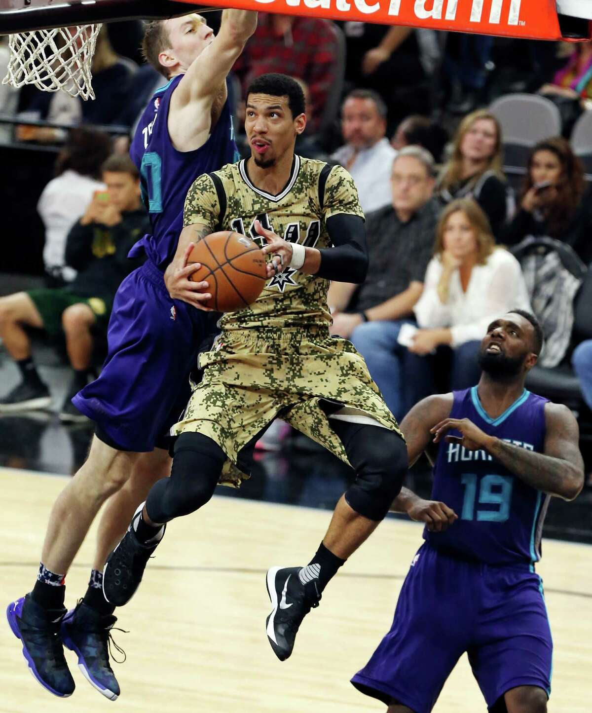 San Antonio Spurs' Danny Green drives to the basket between Charlotte Hornets' Cody Zeller (left) and P.J. Hairston during first half action Saturday Nov. 7, 2015 at the AT&T Center.