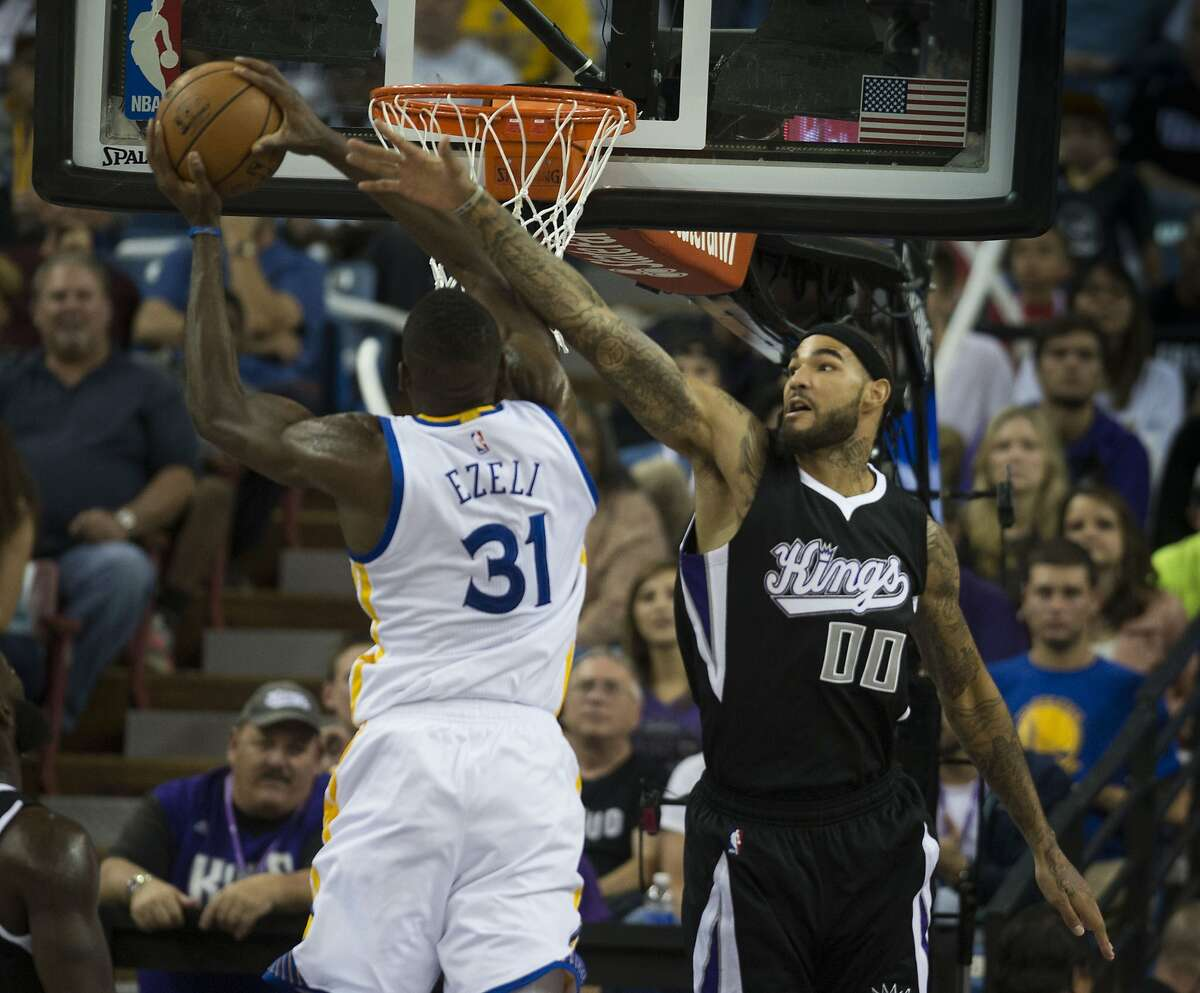 The Sacramento Kings' Willie Cauley-Stein (00) defends the Golden State Warriors' Festus Ezeli (31) as he goes to the basket in the first half at Sleep Train Arena in Sacramento, Calif., on Saturday, Nov. 7, 2015. (Hector Amezcua/Sacramento Bee/TNS)