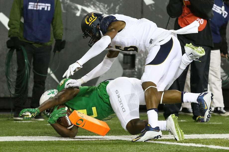 Oregon wide receiver Bralon Addison scores a touchdown after being pushed by Cal cornerback Darius White in the first half of the Bears' loss in Eugene. Photo: Ryan Kang, Associated Press
