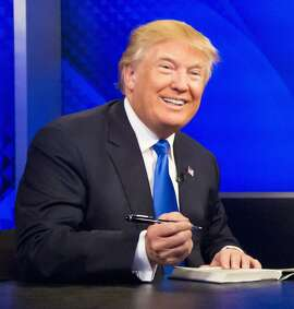 "Republican presidential candidate Donald Trump prepares to sign his book during his appearance on Fox's news talk show ""The O'Reilly Factor,"" Friday, Nov. 6, 2015, in New York. (AP Photo/Bebeto Matthews)"