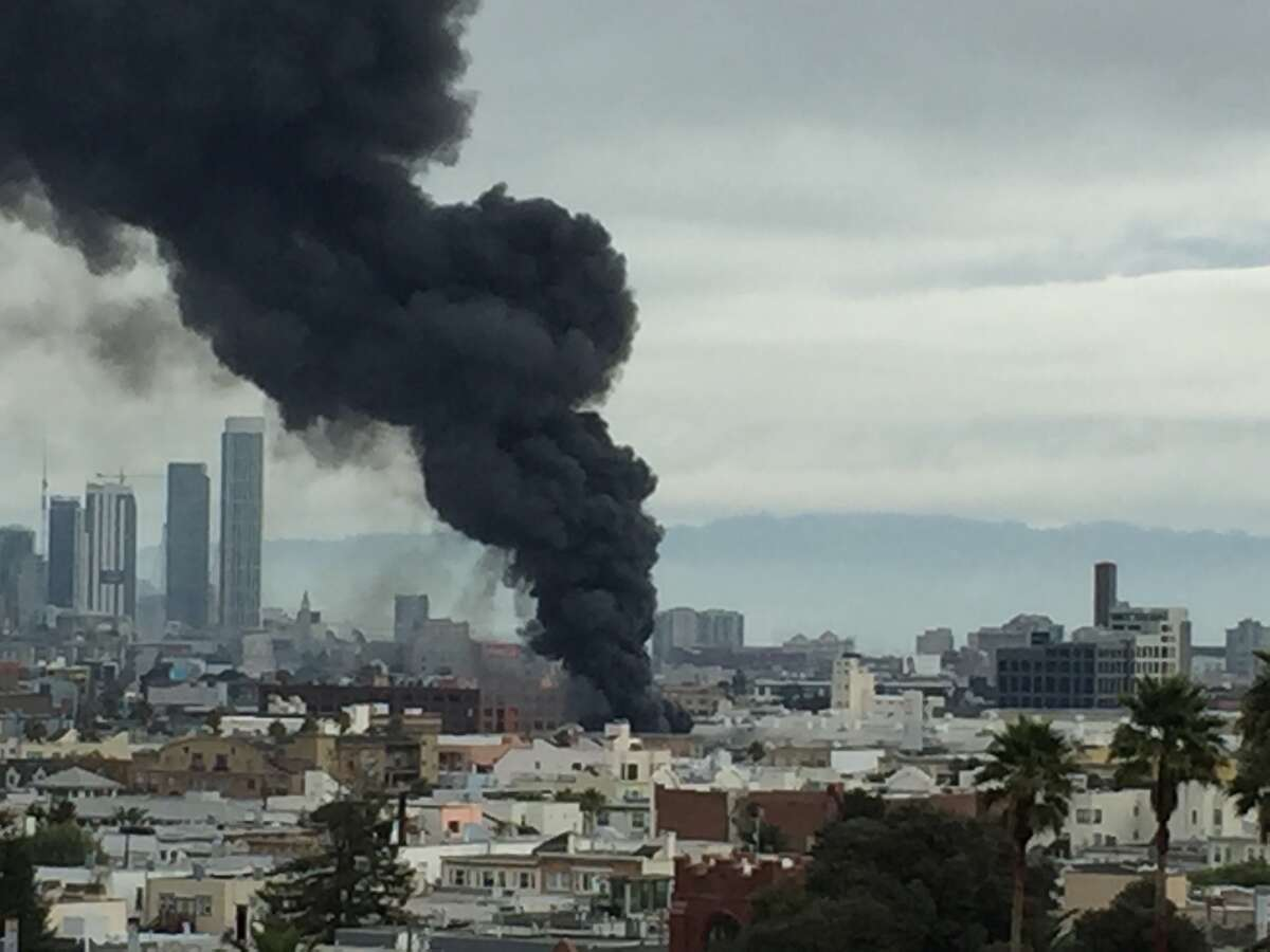 San Francisco firefighters battle a 3-alarm blaze in the city's Mission District on Sunday, November 8, 2015.