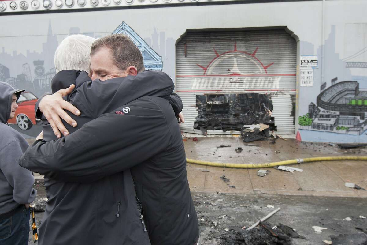 Adam Hassett, right, the Rolling Stock business owner, hugs a man as firefighters battle a 3-alarm fire at 16th and Shotwell streets, Sunday, Nov. 8, 2015, in San Francisco, Calif. The business Rolling Stock was severely damaged and a nearby building was partially damaged.