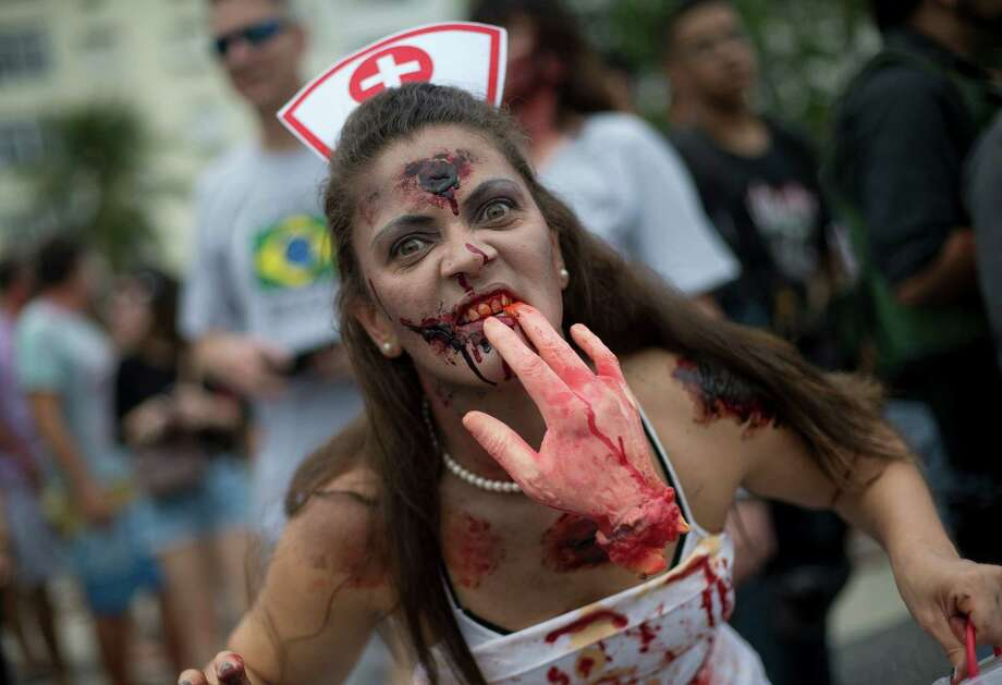 A woman dressed as a zombie nurse gestures to the camera during the Zombie Walk in Rio de Janeiro, Brazil, Monday, Nov. 2, 2015. The annual event was held Monday to commemorate the Day of the Dead. Photo: Silvia Izquierdo, AP / AP