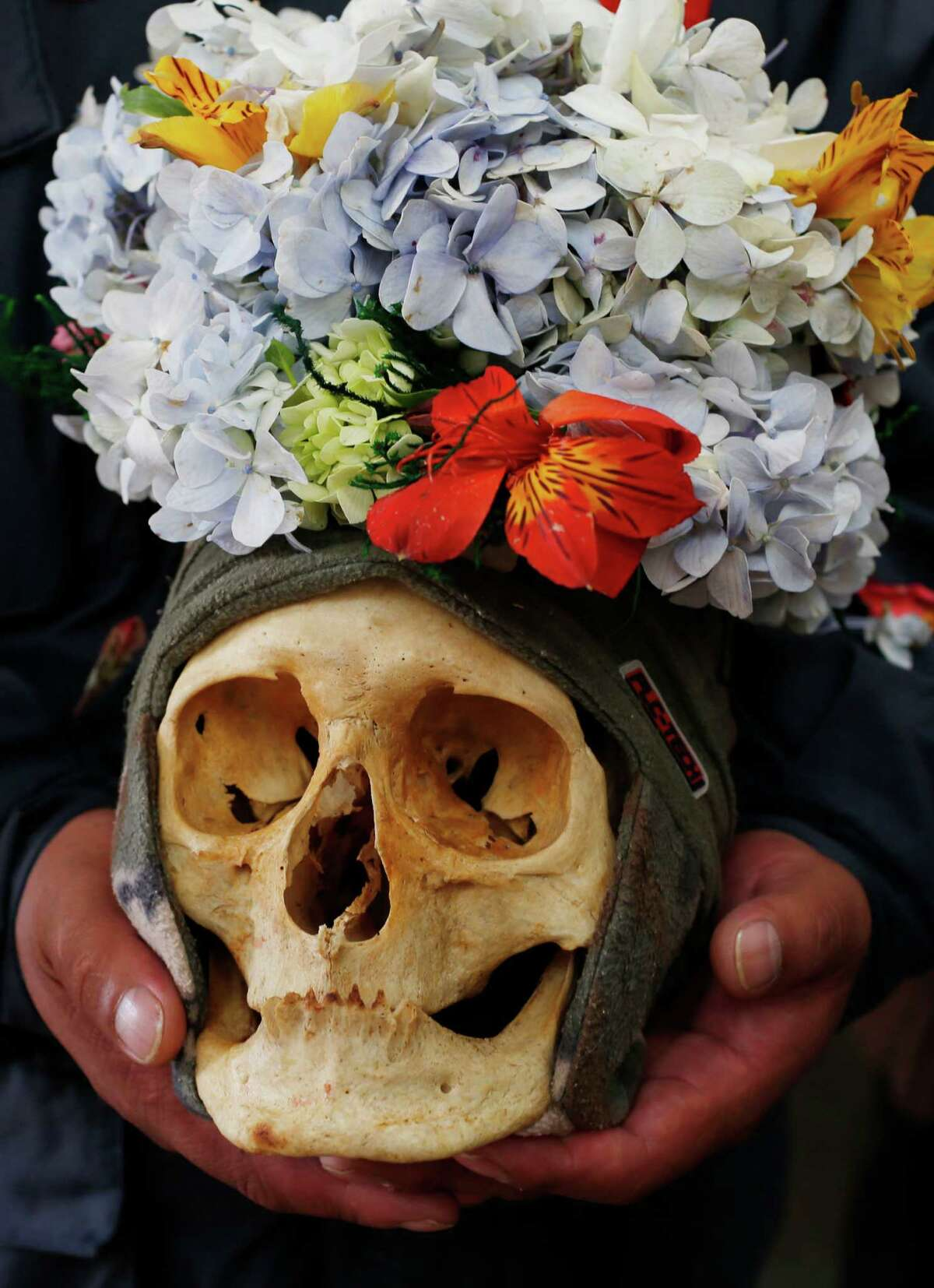 A woman carries decorated human skull or