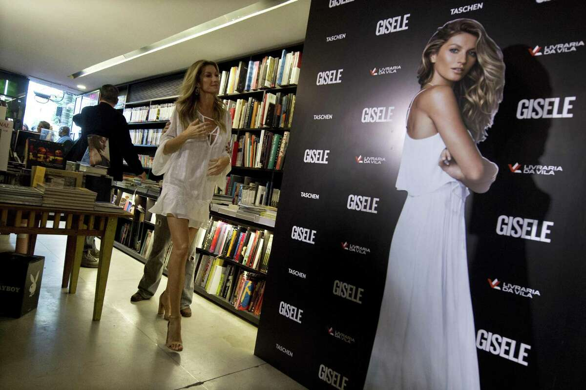 Brazilian supermodel Gisele Bundchen walks next to a real size picture of her, at a bookstore in Sao Paulo, Brazil, where she signed copies of her book