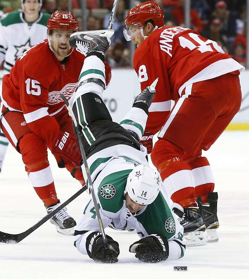Dallas wing Jamie Benn tumbles to the ice after being checked by Detroit's Joakim Andersson (18) in the third period. Photo: Paul Sancya, Associated Press