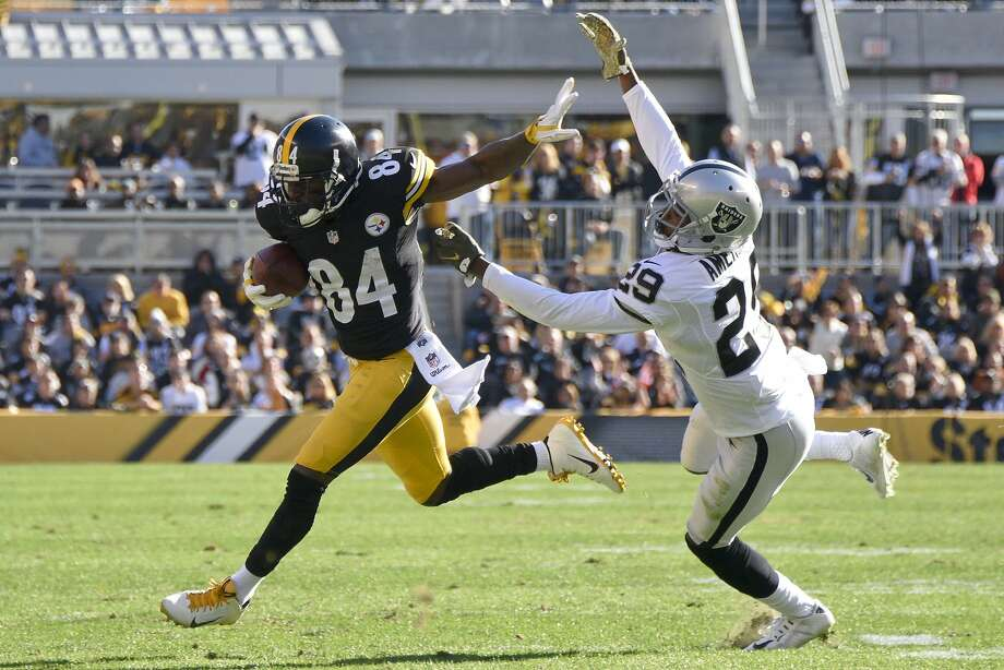 Antonio Brown, who set Steelers records with 17 catches for 284 yards, stiff-arms David Amerson after a second-quarter catch. Photo: Don Wright, Associated Press