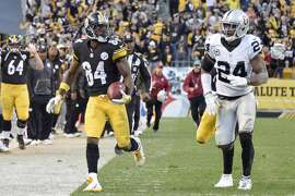 Pittsburgh Steelers wide receiver Antonio Brown (84) runs past Oakland Raiders free safety Charles Woodson (24) after making a catch to help set up the Steelers game-winning field goal in the second half of an NFL football game Sunday, Nov. 8, 2015, in Pittsburgh. (AP Photo/Don Wright)