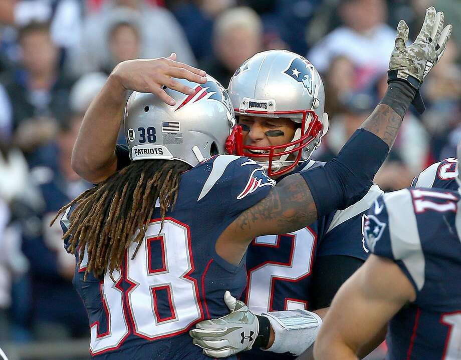 Patriots' running back Brandon Bolden, left, is hugged by Tom Brady after the first touchdown reception of his career. Photo: Jim Rogash, Getty Images